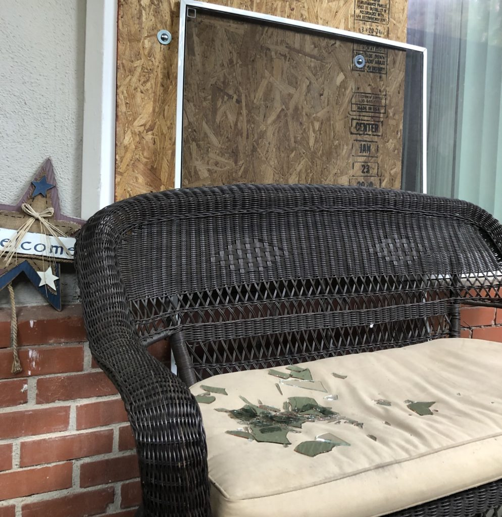 Long Beach police say an officer got in through this broken window, now boarded up, before shooting a woman threatening her mother with a knife. Photo by Jeremiah Dobruck.