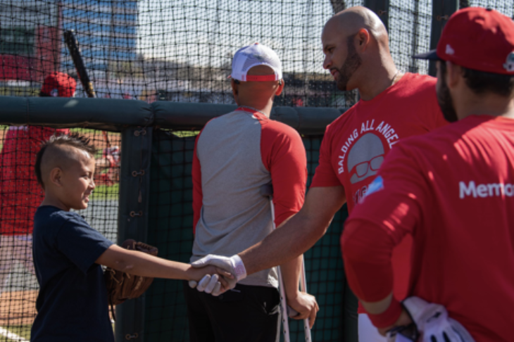 A young boy shakes a baseball player's hand.