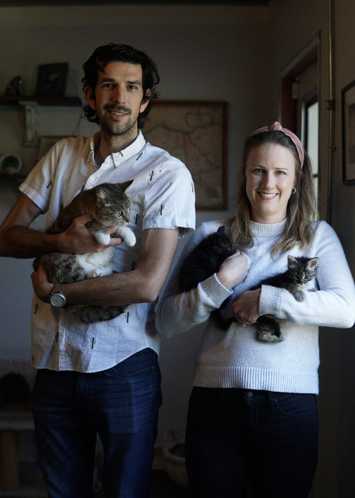 A man with black hair, mustache and white shirt with shorter woman with shoulder-length light-brown hair and white shirt, man holding tabby kitten and woman holding one black and one tabby kitten.