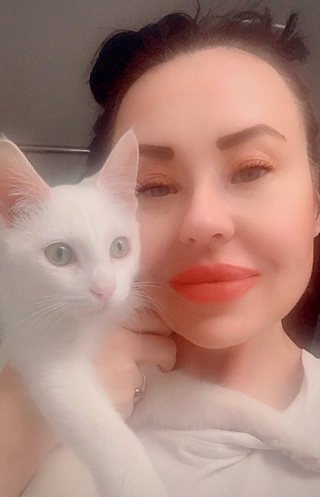 beautiful white kitten with green eyes check to cheek with exotic-looking woman with bright-orange lipstick