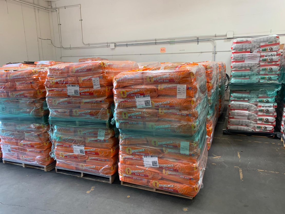 3 piles of large bags of pet food wrapped in plastic sit on pallet, with more behind them.