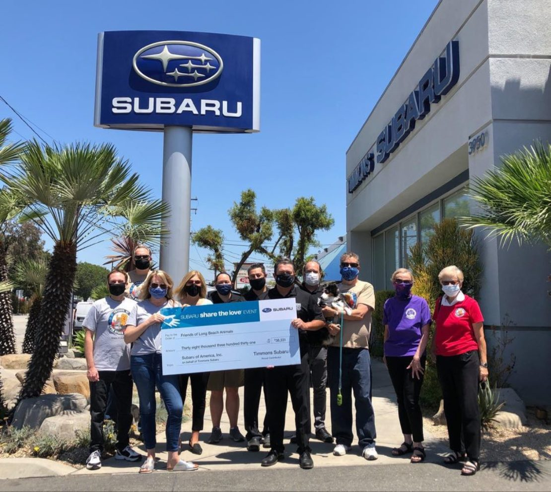 group of 11 people, all wearing masks, stand under Subaru sign holding a huge check for $38,000