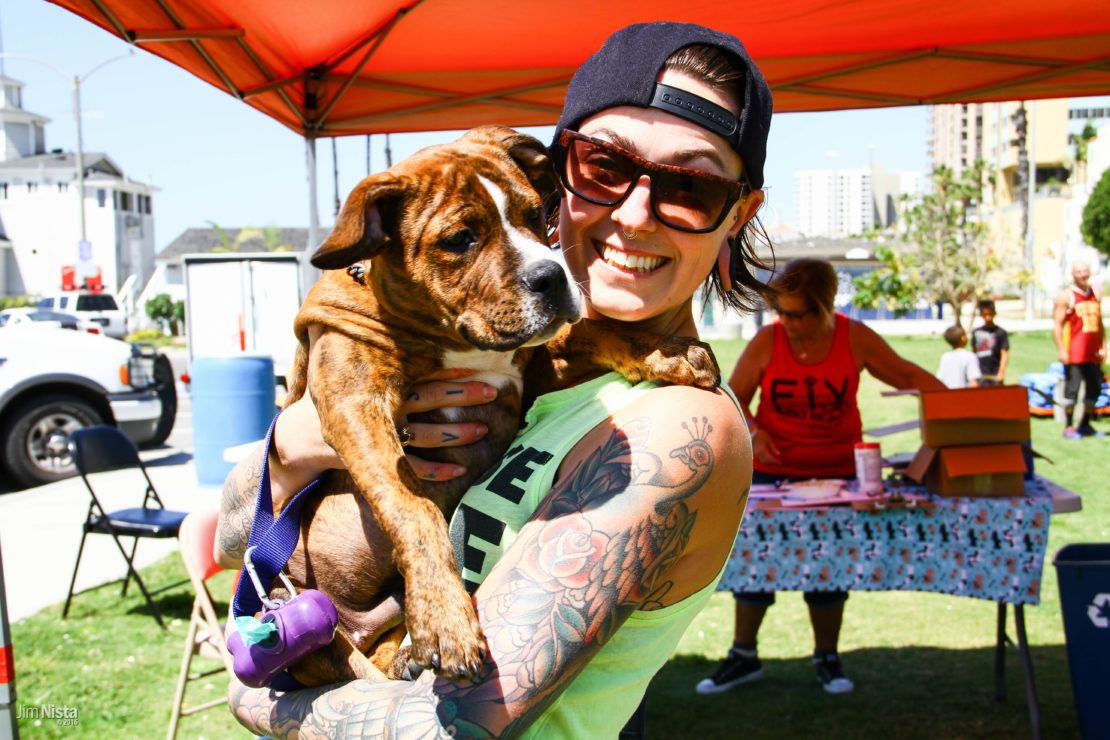 smiling woman in sunglasses, cap and a lot of tattoos holds her brown dog. Red pop-up and volunteer in background