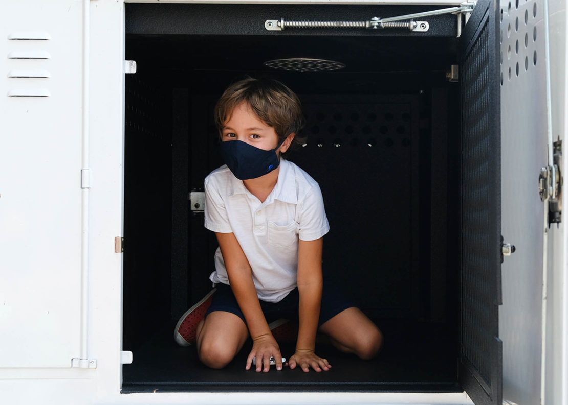 young boy in black mask and shorts and white shirt sits doglike in a kennel in a truck.