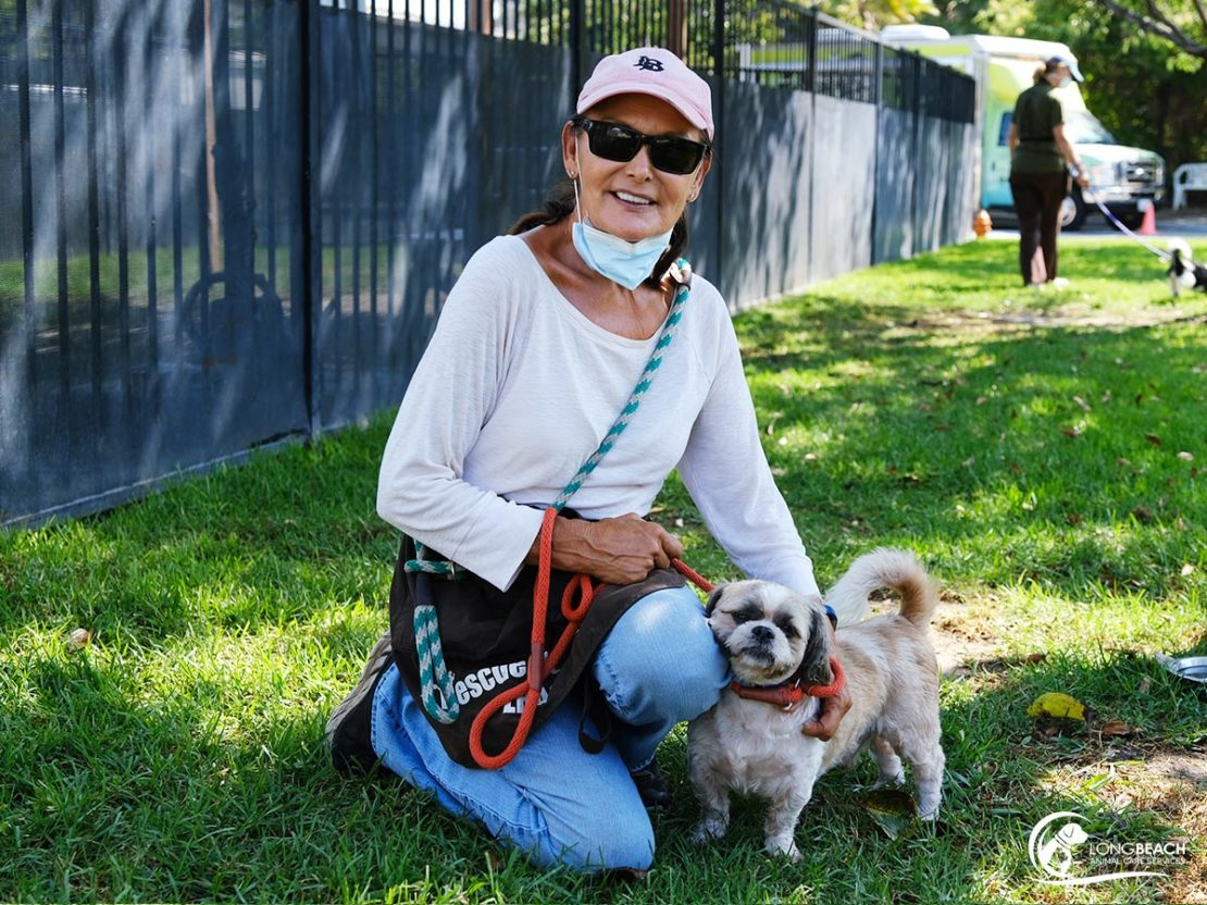 woman in white turtleneck, cap, sunglasses and jeans, with mask at neck, has hand on little white dog. Both sit on grass with cages in background