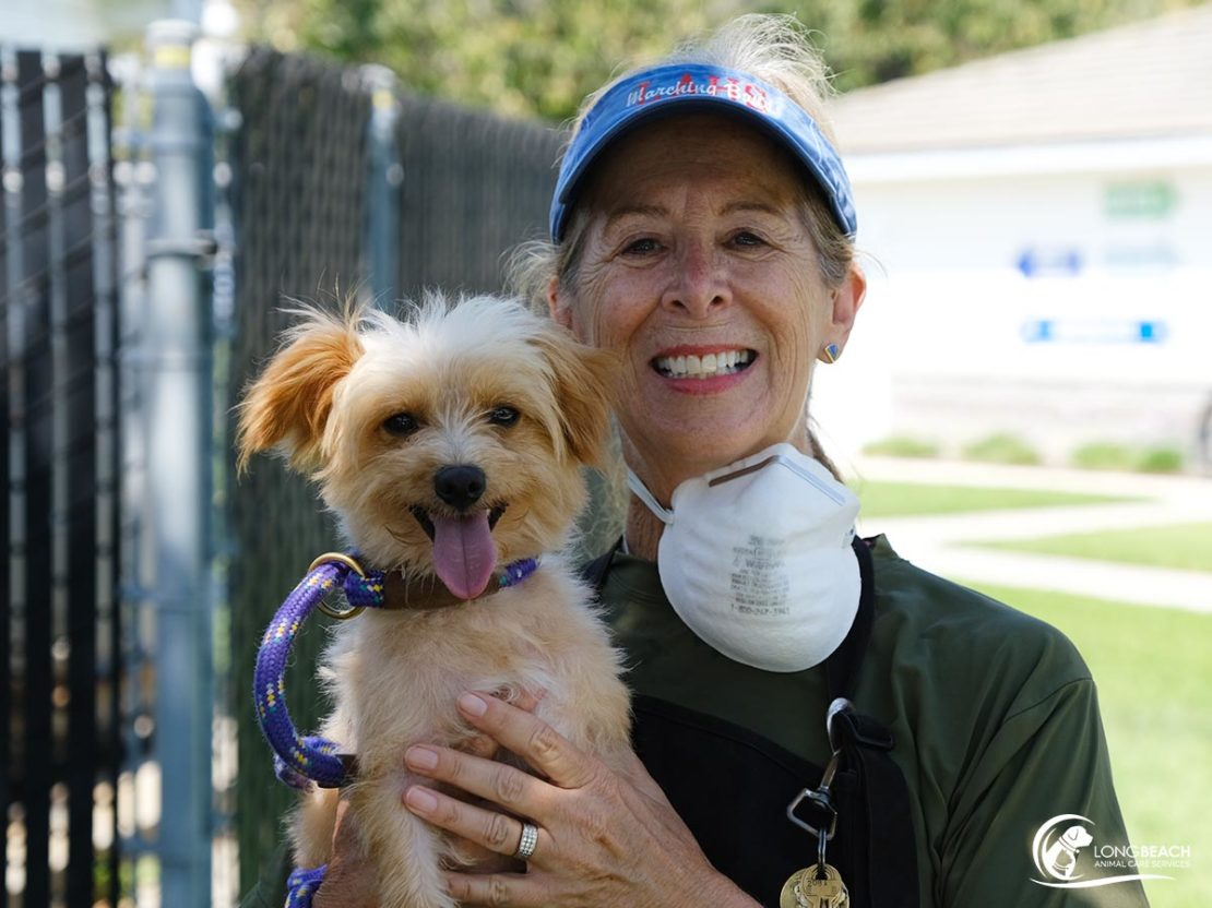 funny-faced tan doggie smiles along wiht a woman with blue cap and mask around neck.