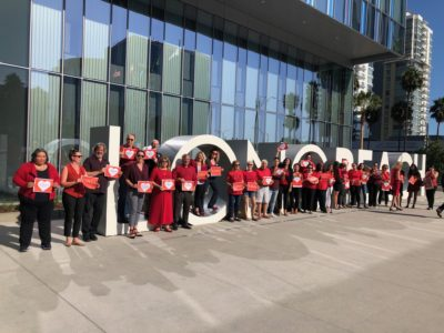 People standing in front of Long Beach City Hall wearing red.