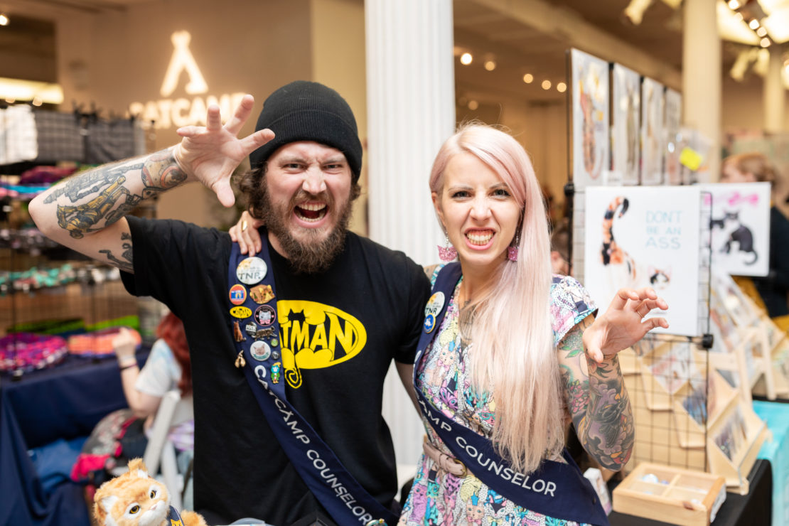 Man in watch cap and black sweatshirt and beard with Cat Man logo and mouth open stands with woman with long, straight pink-silver hair and dress with cats on it, with star in back.