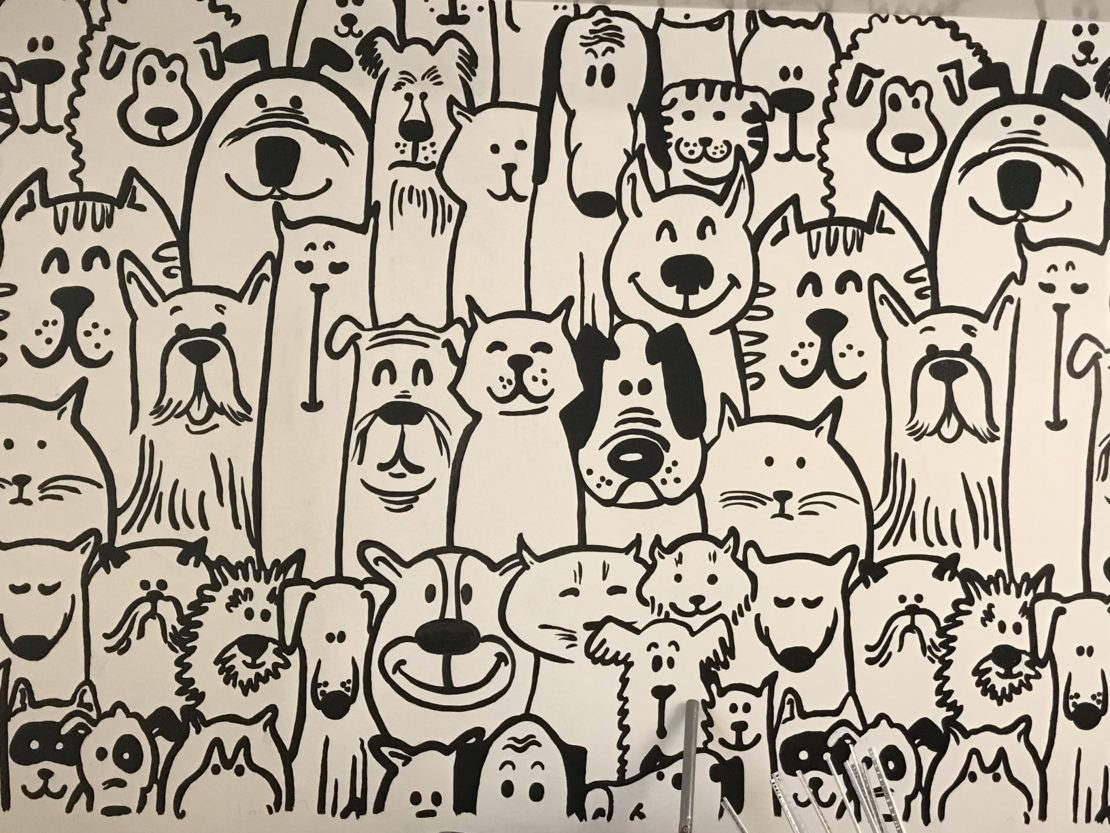 wall decoration featuring cats and dogs rendered in black and white cartoons.