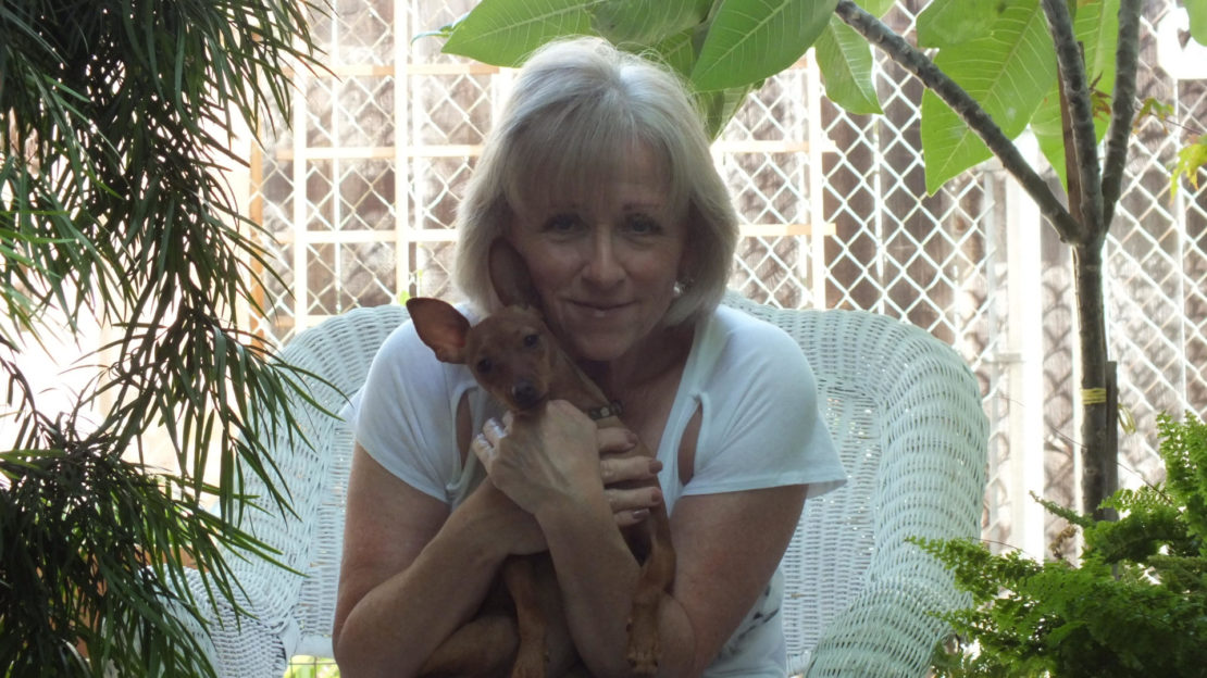 smiling blond woman in white shortsleeve T-shirt holds tiny Chihuahua