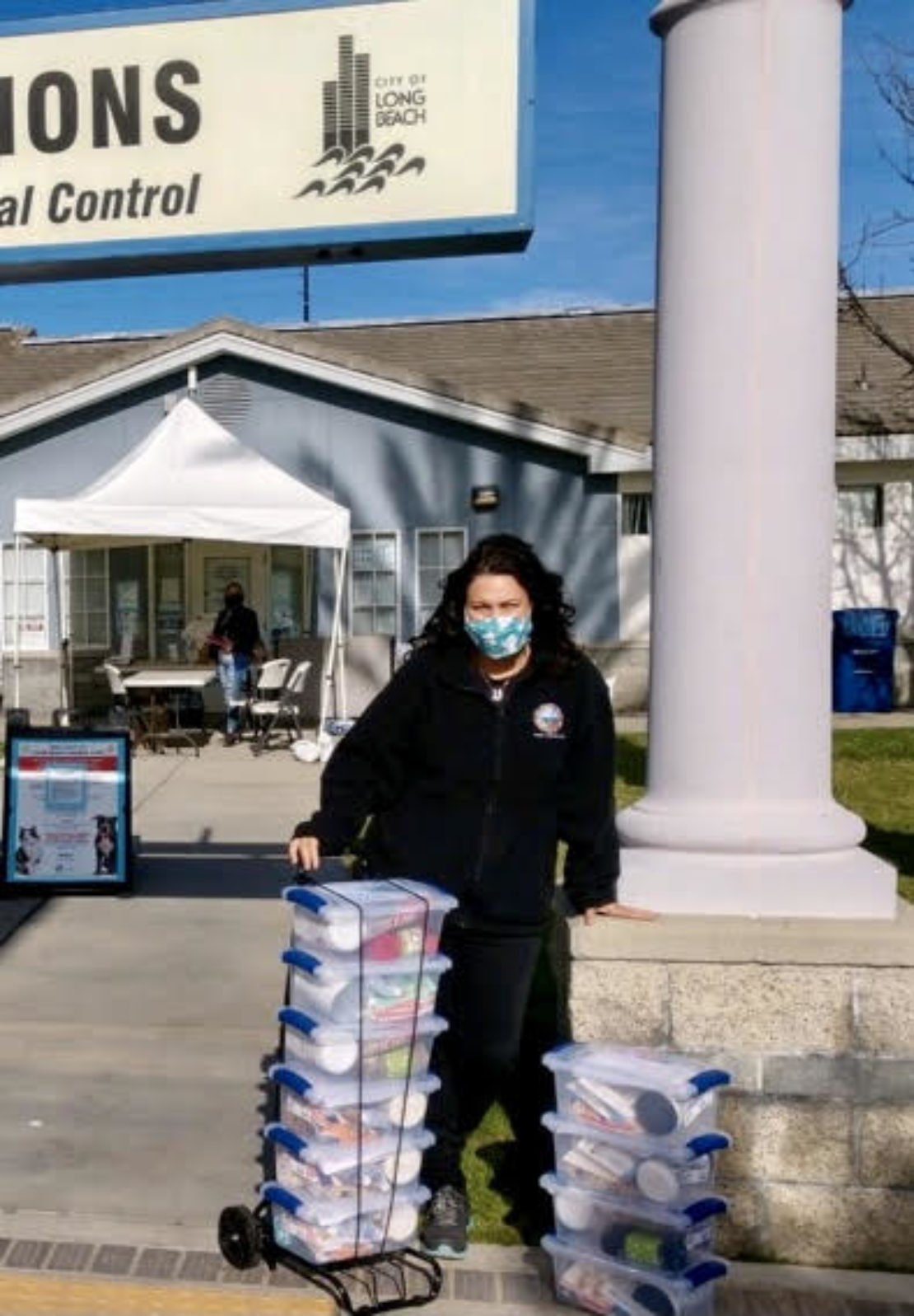 woman in face mask stands next to a pillar in front of a light-blue building next to a large pile of blue boxes.