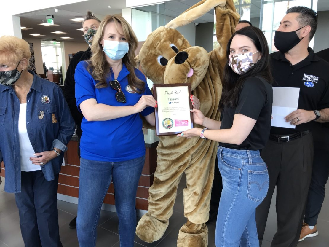 Woman with long blonde hair wearing a blue T-shirt and jeans hands a plaque to woman in white mask with black hair and wearning jeans. Person in brown dog costume stands between them.
