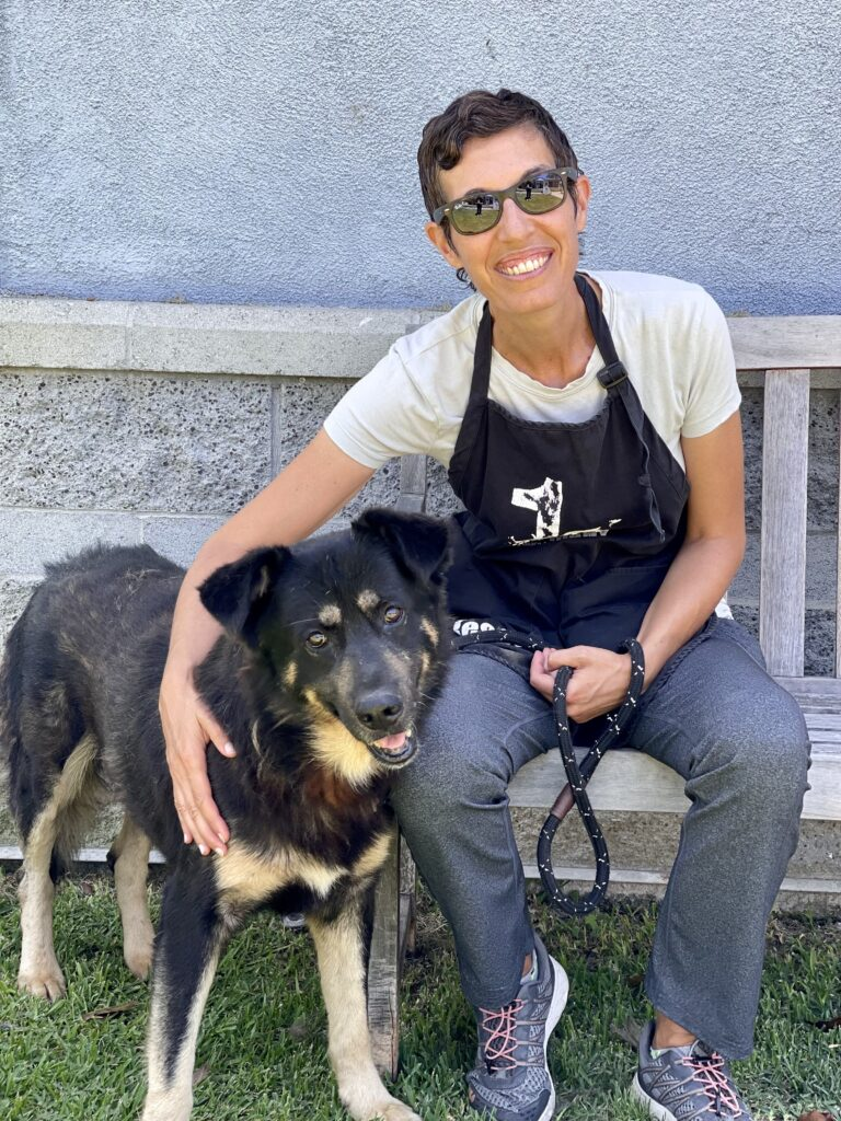 smiling woman with short, black hair and wearing sunglasses, a green apron, a white shirt and blue jeans sits on a bench next to a large, black dog with a tan chest and legs in front of a blue-and-beige building.