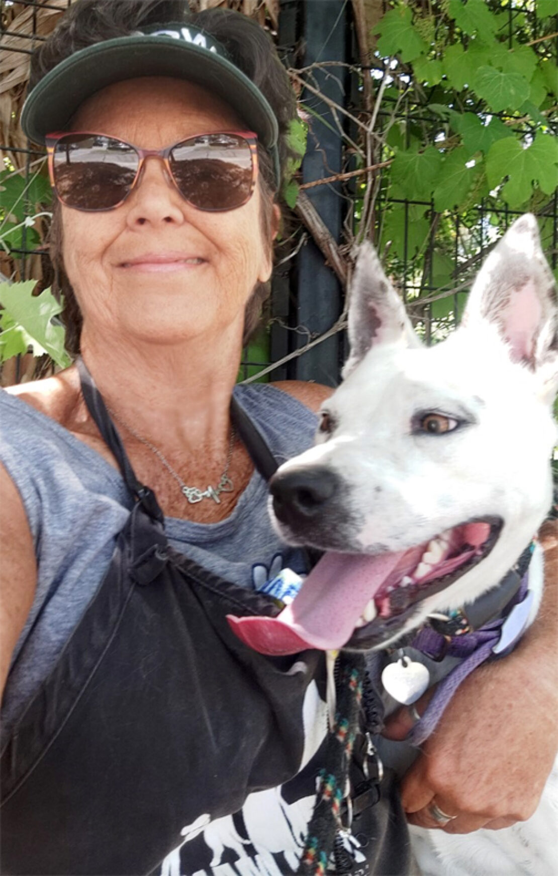 smirking woman in sunglasses and black cap and apron has arm around a white German shepherd mix. Photos are from chest up.