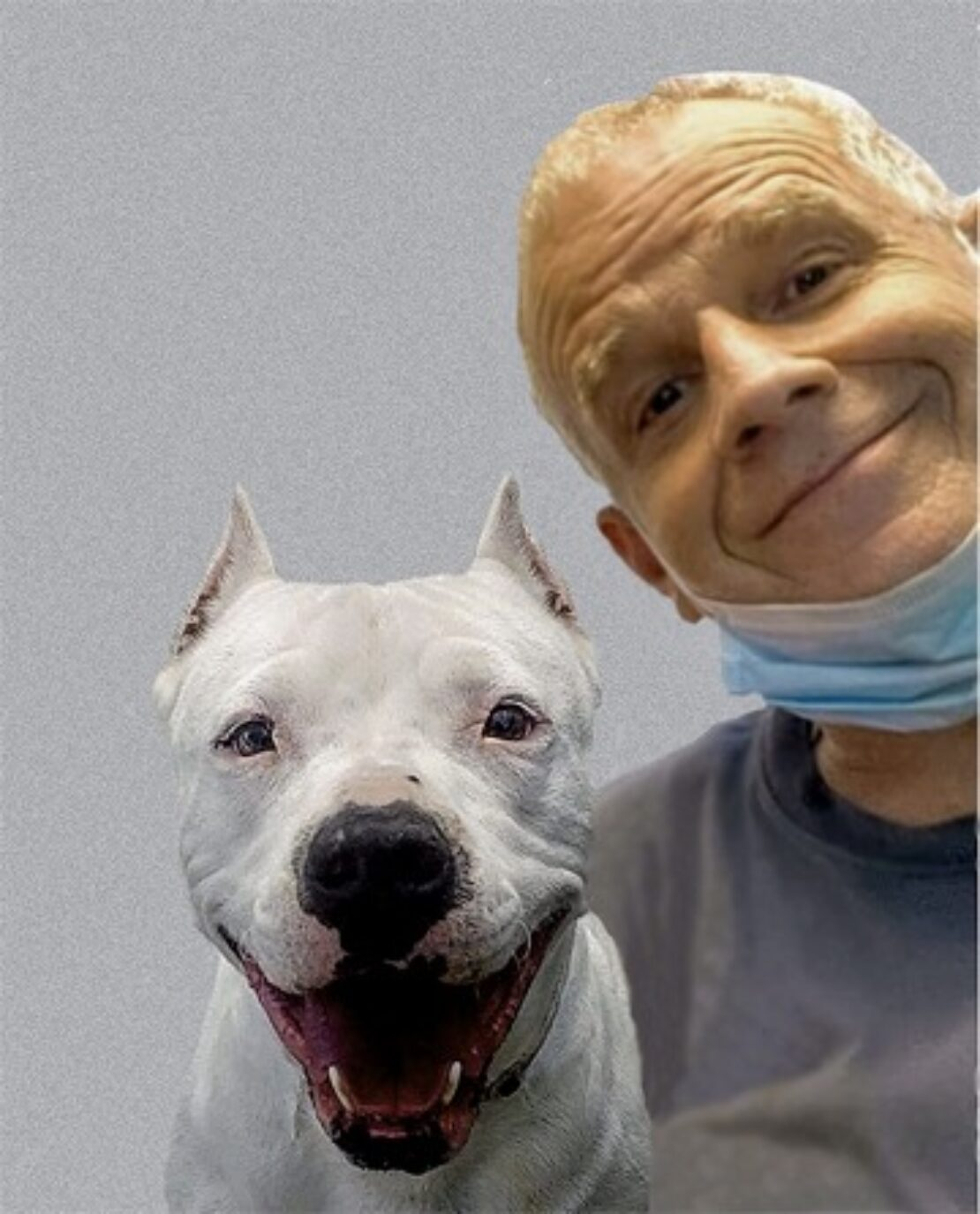 smiling man with gray hair and gray shirt and mask around neck poses next to a white dog.