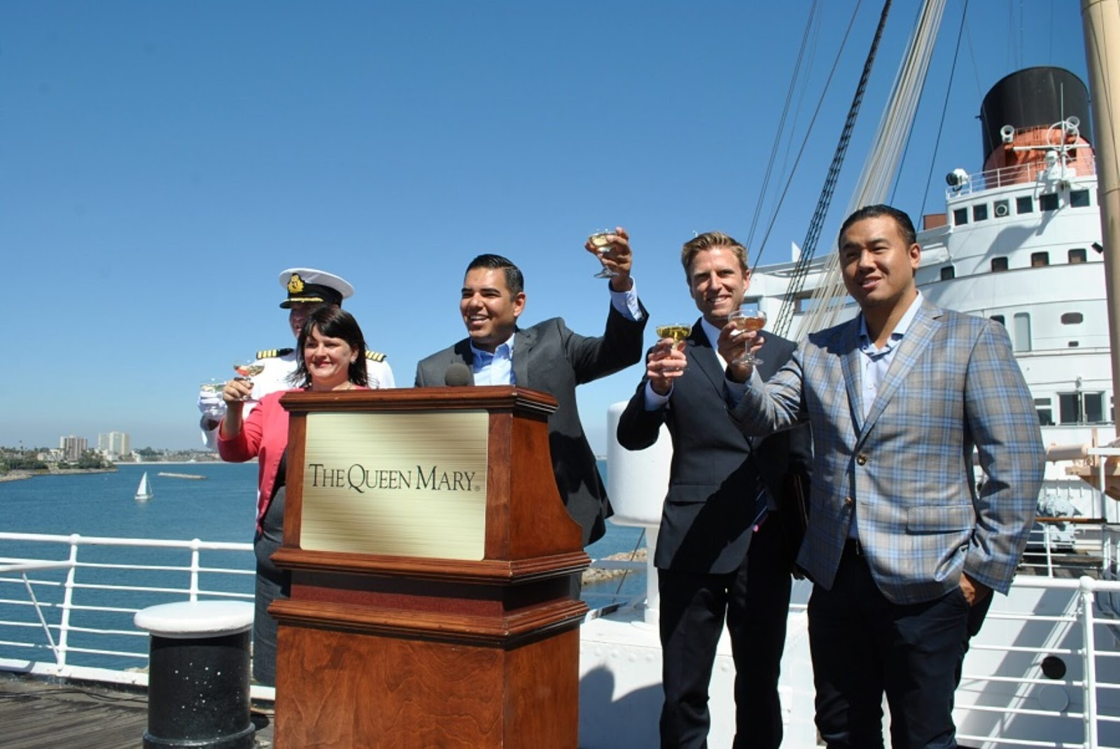 From left, Queen Mary Honorary Commodore Everett Hoard, former District 2 Councilwoman Jeannine Pearce, Long Beach Mayor Robert Garcia and Urban Commons Principals Taylor Woods and Howard Wu celebrate on the Queen Mary in 2016. Photo by Asia Morris.