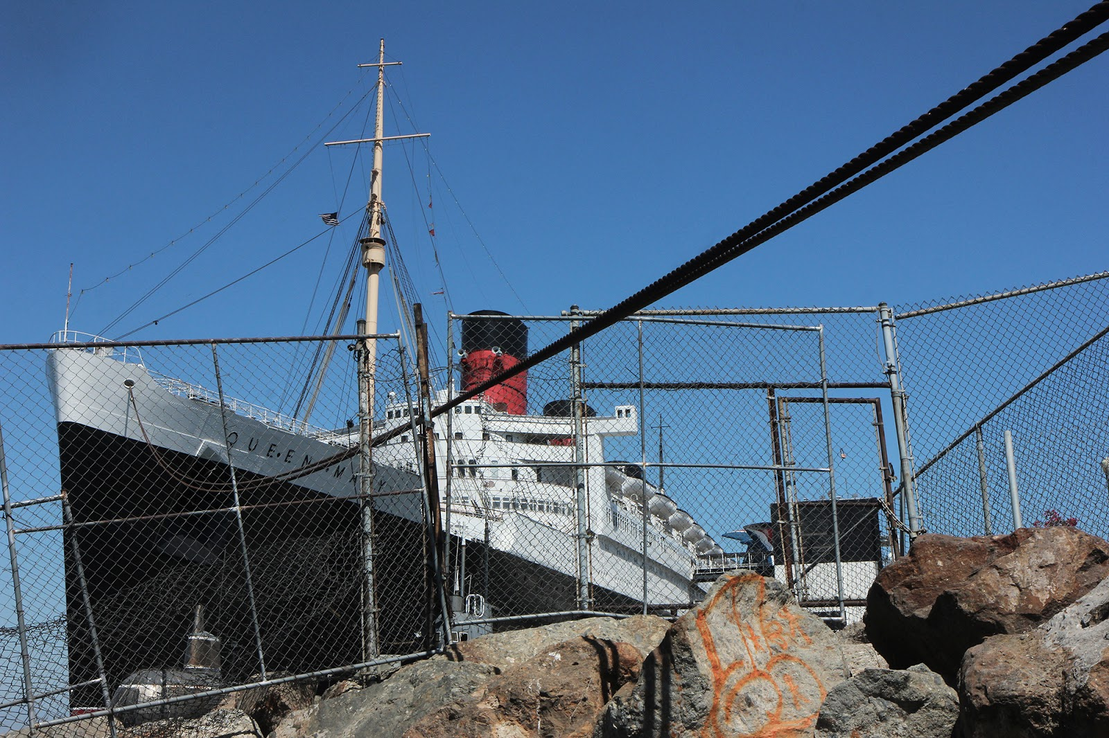 A fence keeps people off of the rocky barrier surrounding the Queen Mary in Downtown Long Beach, Thursday, June 10, 2021. Photo by Brandon Richardson.